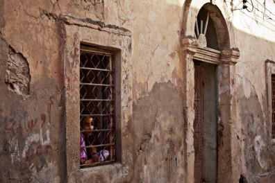 A girl looks out of her house window in Benghazi, Libya. Photo: UNSMIL (file)
