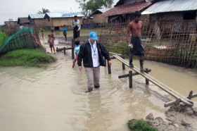 In Myanmar, a UNHCR staff member wades through a flooded section of Nget Chaung camp for internally displaced persons (IDPs) in Pauktaw township, Rakhine State, to assess the damage and identify needs caused by Cyclone Komen. Photo: UNHCR/Saw Lian Bik