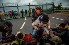 French gendarmes try to separate migrants on the Eurotunnel site near the boarding docks in Coquelles near Calais, northern France, on late July 29, 2015. One man died Wednesday in a desperate attempt to reach England via the Channel Tunnel as overwhelmed authorities fought off hundreds of migrants, prompting France to beef up its police presence. AFP PHOTO / PHILIPPE HUGUEN