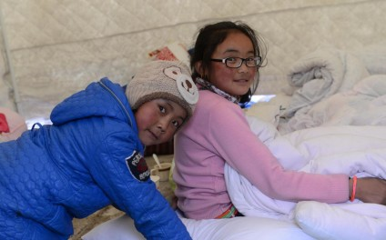 (150426) -- NYALAM, April 26, 2015 (Xinhua) -- Two children are relocated in a temporary tent in Nyalam County of Xigaze Prefecture, southwest China's Tibet Autonomous Region, April 26, 2015. Death toll in southwest China's Tibet Autonomous Region has climbed to 17, after a powerful earthquake struck neighboring Nepal on Saturday. Some 7,000 people have been relocated in the county of Nyalam, while about 5,000 have been evacuated in the county of Gyirong. (Xinhua/Chogo)(mcg)